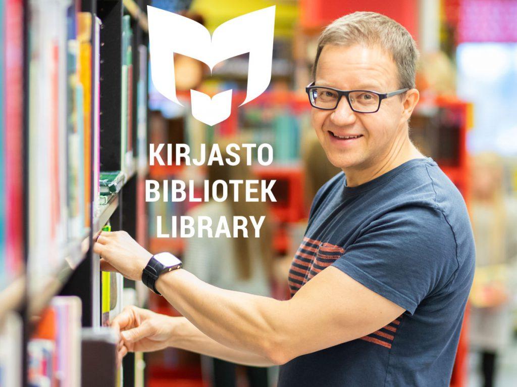 Hymyilevä kirjaston työntekijä kirjahyllyn edessä.