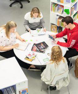 Nuoret opiskelijat pyöreän pöydän ääressä.