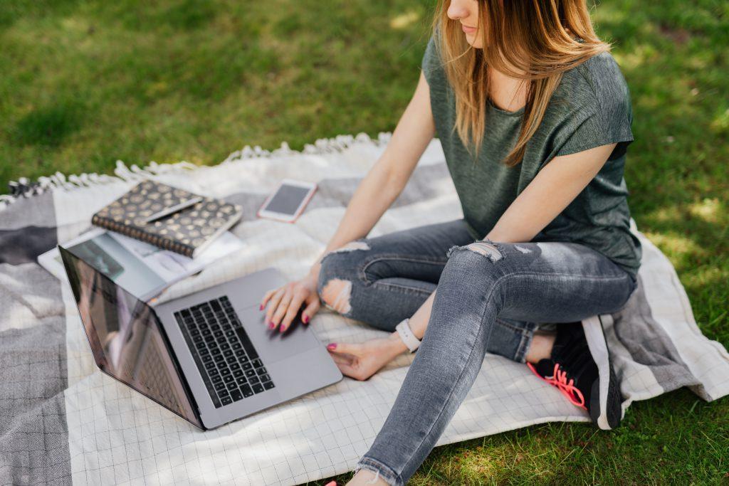 Nainen nurmikolla kannettavan tietokoneen kanssa.